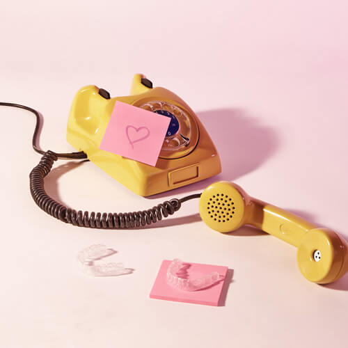 Telefone amarelo com um aparelho transparente ao lado