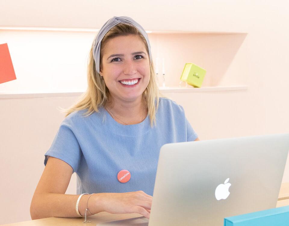 Uma dentista da SouSmile sorrindo em frente ao computador